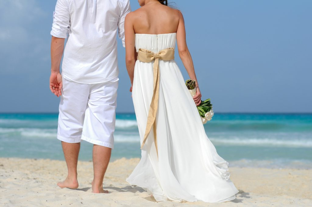 A wedding couple walking on the beach and holding hands